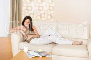 Young woman with magazine and coffee in lounge