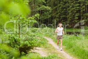 Sportive man jogging in nature by lake
