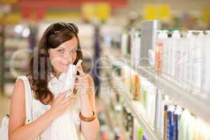 Shopping cosmetics - woman smelling shampoo