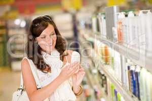 Shopping cosmetics- smiling woman holding shampoo
