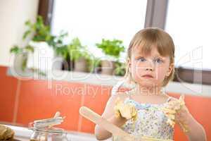 Child baking - little girl kneading dough