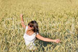 Happy young woman in corn field enjoy sunset