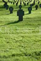 Grass field with crosses during  sunset, cemetery
