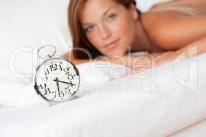 White lounge - Alarm clock standing on bed, woman in background