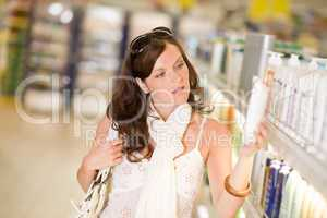 Shopping cosmetics - thoughtful woman choose shampoo