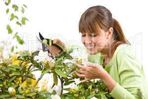Gardening - woman cutting flower with pruning shears