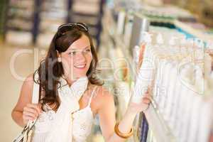 Shopping cosmetics - smiling woman choose shampoo