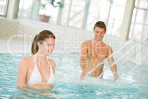 Swimming pool - young couple have fun under water stream