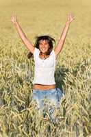 Happy woman jump in corn field in summer