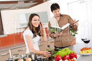 Happy couple cook in kitchen with cookbook