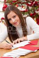 Young woman thinking while writing Christmas card