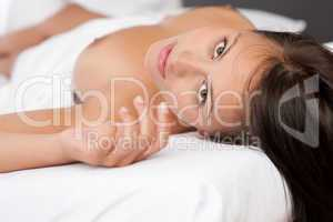 Young brown hair woman lying in white bed