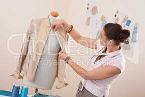 Female fashion designer taking measurement