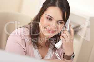 Portrait of young businesswoman on phone at office