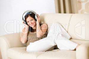 Happy woman with headphones on sofa in lounge