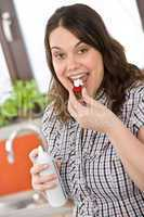 Plus size woman with whipped cream on strawberry in kitchen