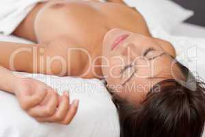 Naked woman sleeping in white bed, shallow DOF