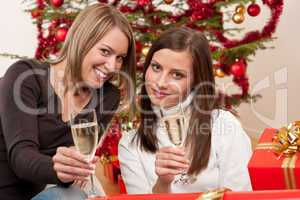 Two young woman with champagne and Christmas tree