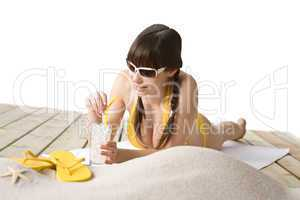 Beach - woman with cold drink in bikini sunbathing