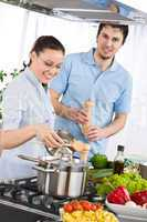 Happy couple cooking in modern kitchen
