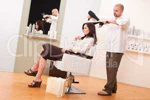 Professional hairdresser with hair dryer at salon with customer