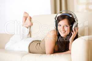 Happy woman with headphones lying down on sofa  in lounge