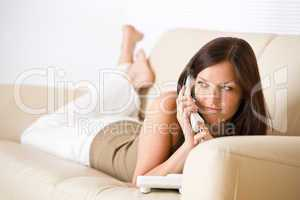 On the phone: young woman calling in lounge