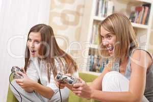 Students - Two happy female teenager playing TV game