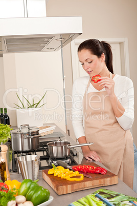 Happy woman biting red pepper in modern kitchen