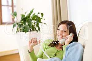 On the phone home: Smiling woman calling in lounge