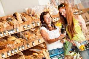 Grocery store: Two women choosing wine