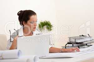 Female architect with laptop sitting