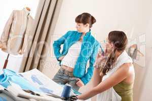 Fashion model trying turquoise jacket in designer studio