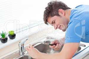 Self-assured man repairing his sink in the kitchen