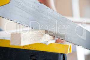 Close-up of a worker sawing a board