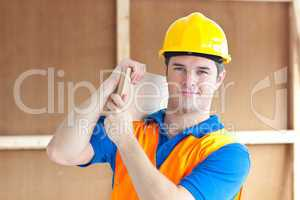 male worker with a yellow helmet carrying a wood