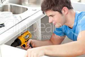 man holding a drill repairing kitchen