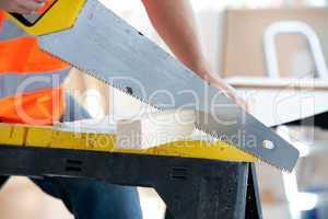 male worker sawing a wooden board