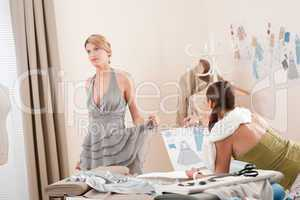 Fashion model fitting dress by professional designer