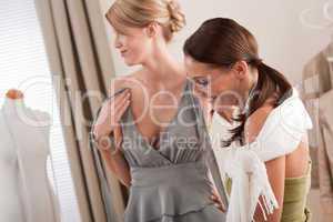 Fashion model fitting gray dress by designer