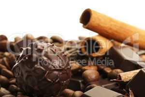 trüffel vor kaffeebohnen und zimtstangen auf schokoladentafel