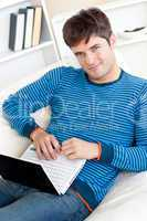man working on his laptop lying on the couch