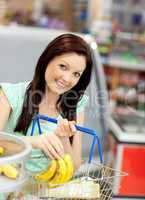 woman putting bananas in her shopping-basket