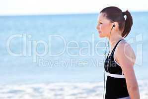 woman listening music on the beach