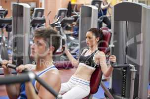 couple using shoulder press in a fitness centre