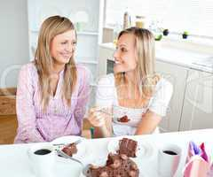 two women eating a chocolate cake