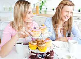 Women eating cupcakes in the kitchen