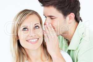 man whispering something to his female friend