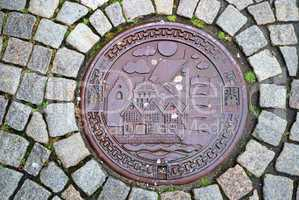 Sewer manhole on stone pavement of Trondheim.