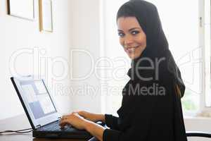 A Middle Eastern woman sitting in front of a computer at home